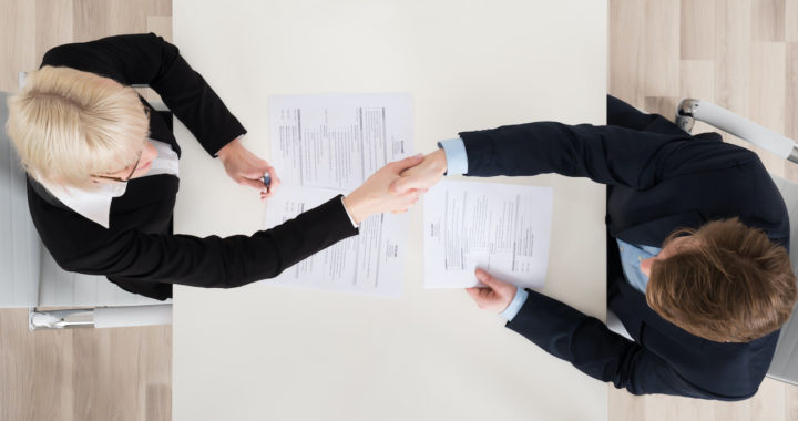 Lawyers Shaking Hand At Desk