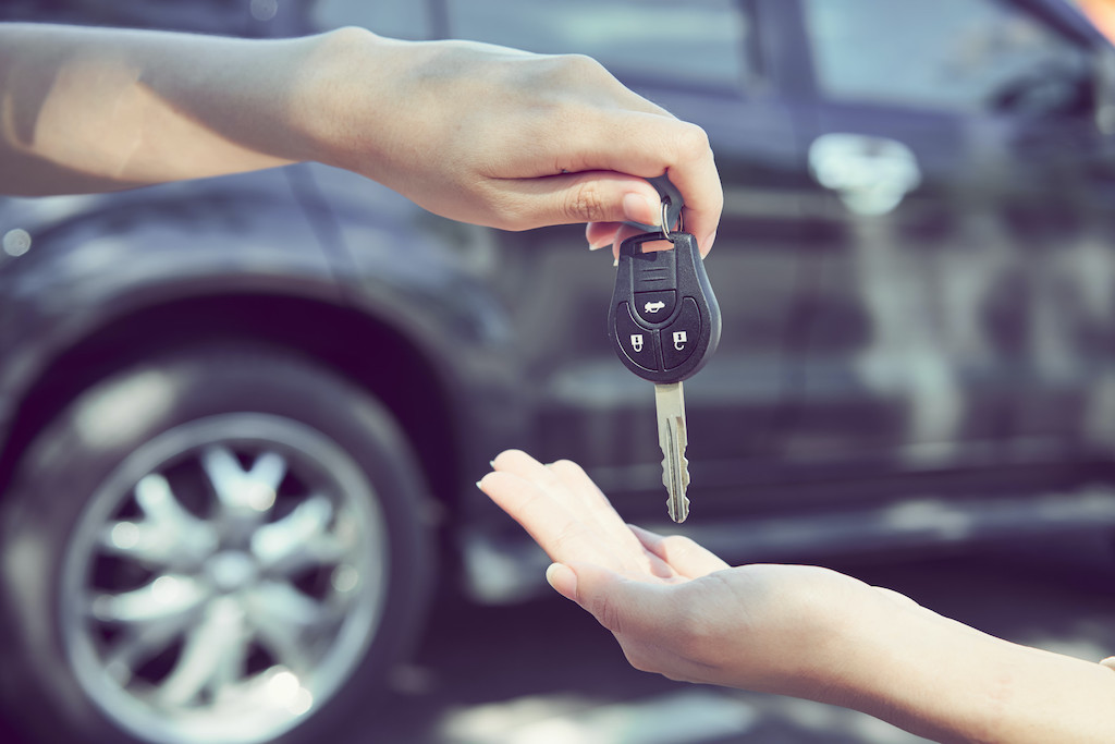 Woman's hand give the car keys